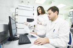 Researchers analyzing liquid chromatography data Stock Photo