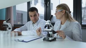 Researchers microscoping in biochemistry lab. Attractive female supervisor in goggles and her male mixed race assistant analyzing microscope slides in research stock footage