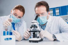 Researchers in white coats and medical masks working with reagents together. In lab stock photography