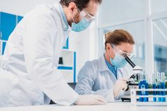 Researchers in white coats and medical masks working with reagents together. In lab royalty free stock photos