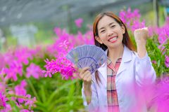 Researchers women, are glad to succeed in pink orchid orchards in the garden for export. Researchers, women, are glad to succeed in pink orchid orchards in the stock image