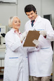 Researchers Writing On Clipboard In Laboratory. Male and female researchers writing on clipboard in medical laboratory Stock Images