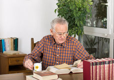 Researching in old books. Senior man found newspaper clipping in old books Royalty Free Stock Photos
