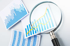 Researching and reading data with magnifying glass. Royalty Free Stock Photos
