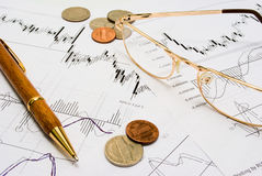 Researching stock trends. Snapshot of charts, coins, glasses and a pen Royalty Free Stock Photo