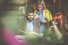 Researching together at cafe. Business people. Business colleagues at cafe researching together and reading book. Business people Royalty Free Stock Photo