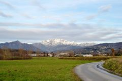 Resegone mountain range covered with snow and green grass fields of Brianza countryside. Beautiful panoramic view from Molteno to Resegone mountain range stock images