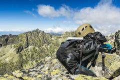 Resehandbok, mörk kaki- hjälm och en svart ryggsäck i bergen royaltyfria bilder