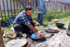 Resen, македония 18-ое мая 2016 - молодой путешествуя ремесленник retinning старое медное блюдо в деревне Carev Dvor, Resen, маке Стоковые Изображения RF