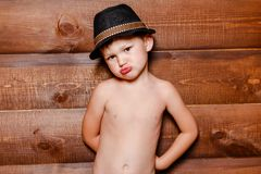 Resentful boy in hat on the background of wooden wall stock images