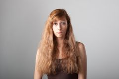 Resentful casual girl on gray. Resentful casual caucasian girl with long brown hair on gray background Royalty Free Stock Photography
