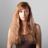 Resentful casual girl on gray Stock Image