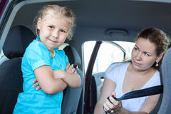 Resentful child ignoring mother forcing to seat into infant safety seat. Resentful child ignoring mother forcing to seat into infant car safety seat Royalty Free Stock Image