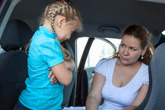 Resentful child refusing get in safety seat under mother severe look Royalty Free Stock Photo