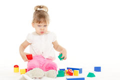 Resentful girl with educational toys. Little resentful girl plays with children blocks set on a white background. Learning toys and early development Stock Photos