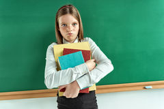Resentful little girl hugging school books. Stock Photography