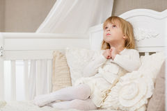 Resentful little girl. Resentful pretty little girl sits on a sofa in the room Royalty Free Stock Photo