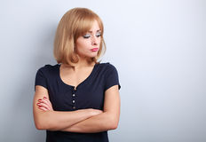 Resentful unhappy casual woman with short blond hair looking dow. N on blue background Stock Images