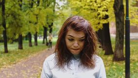 Resentful young redhead woman in a park stock video footage