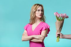 Resentful young woman receiving flowers apology. I am sorry. Offended girl is looking bouquet of tulips in male hand with hesitation. She is standing with Royalty Free Stock Photography