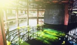 Reserva de agua con agua verde de la torre de enfriamiento abandonada en luz del sol Imagen de archivo libre de regalías