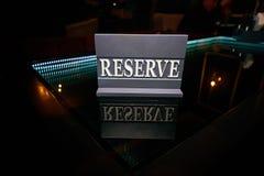A reserva de madeira do sinal está em uma tabela de vidro preta fotografia de stock