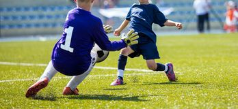 Reserva joven del portero del fútbol Balón de fútbol de cogida del muchacho Fotos de archivo