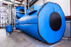 Reservatórios azuis grandes na sala de caldeira da fábrica foto de stock