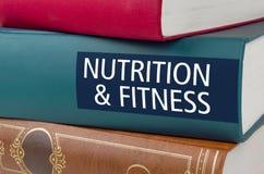 Reserve con la nutrición y la aptitud del título escritas en la espina dorsal imagenes de archivo