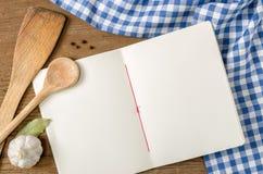 Reserve con las cucharas de madera en un mantel a cuadros azul Fotografía de archivo libre de regalías