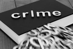 Reserve la novela con el crimen de la palabra y las letras borrosas que salen de las páginas Fotografía de archivo libre de regalías