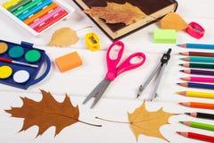 Reserve, los accesorios de la escuela y las hojas otoñales, de nuevo a concepto de la escuela Foto de archivo