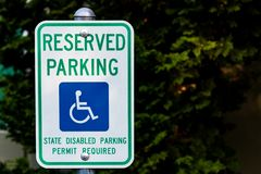 Reserved handicapped permit parking only sign. In front of green bushes royalty free stock image
