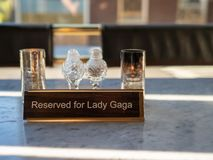 Reserved for Lady Gaga sign sitting on marble restaurant table with candles with salt and pepper shakers royalty free stock image