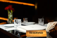 Reserved plate on a table. With flowers in restaurant Stock Photos