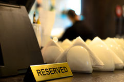 Reserved sign and crockery on a bar counter Royalty Free Stock Photos