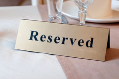 Reserved sign, reservation. On table. Beige color Royalty Free Stock Photo