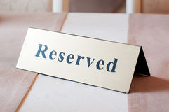 Reserved sign, reservation. On table. Beige color Stock Image