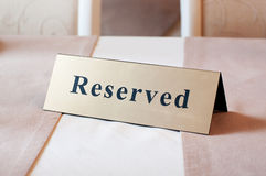 Reserved sign, reservation. On table. Beige color Royalty Free Stock Image