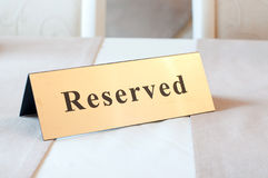 Reserved sign, reservation. On table. Gold color Stock Images