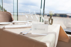 Reserved sign on restaurant table with sea view Stock Photography