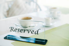 Reserved sign on a table in restaurant. With cups of coffee on background Stock Images