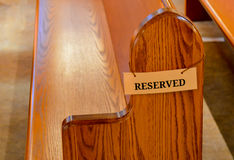 Reserved Seating. A single oak wood church pew with a very simple tag stating reserved but only our imagination can figure out who it would be reserved for royalty free stock photography