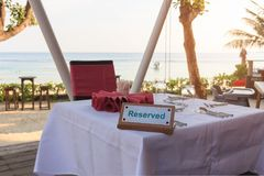 Reserved table dinner time. Reserved table dinner time in luxury restaurant on sea background Royalty Free Stock Photo