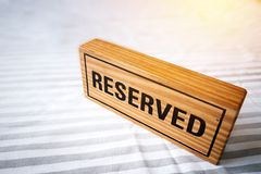 Reserved table. reserved wooden sign on table for reservation pl Royalty Free Stock Photos