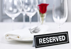 Reserved table at romantic restaurant. Reserved romantic restaurant table setting with roses plates and cutlery Royalty Free Stock Photography