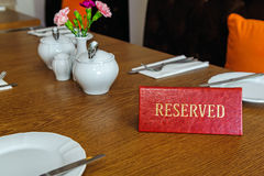 Reserved table. Reserved sign on a restaurant wooden table Royalty Free Stock Images