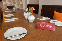 Reserved table. Reserved sign on a restaurant wooden table Stock Images