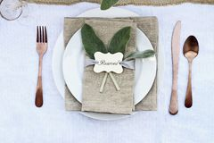 Reserved Place Setting. Reserved Thanksgiving or Halloween place setting with Lamb`s Ears leaves and copper utensils. Image shot from above stock photo