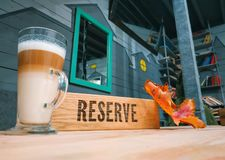 Reserved wooden sign in a restaurant with autumn leaf in cafe stock image